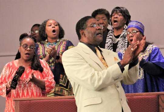 Henry Flint stands and claps along with the New Light Baptist Church choir at Sunday's dedication service to radio station KVVO, which offers traditional gospel music.