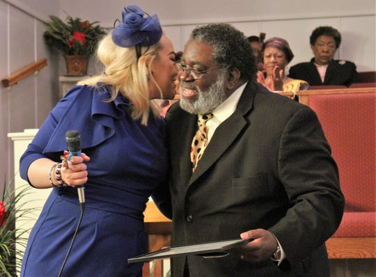 Crystal King, KVVO deejay, presents Bishop Warren D. Coble Sr. with a plaque and hug for giving the sermon at Sunday's dedication service for Abilene's black radio station.