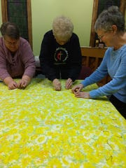 From left: Cindy Minus, Linda Merritt and Karon Lewis sew a quilt at Fairview United Methodist Church in Binghamton. They are members of My Brothers Keeper, a group which sews quilts and gives them away to homeless people.