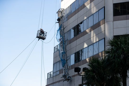 Crews lower scaffolding dangling from the building known as Frost Bank Plaza on Monday, Feb. 17, 2020.