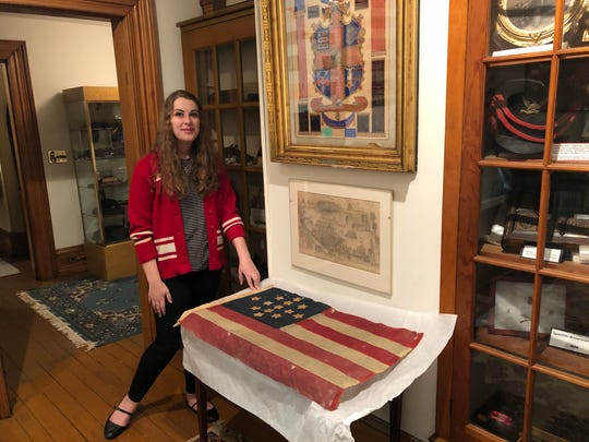 Katie D'Aquilante, museum coordinator for the Gloucester County Historical Society, shows a flag that was sewn by the wife of a Revolutionary soldier who fought at the Battle of Fort Mercer.