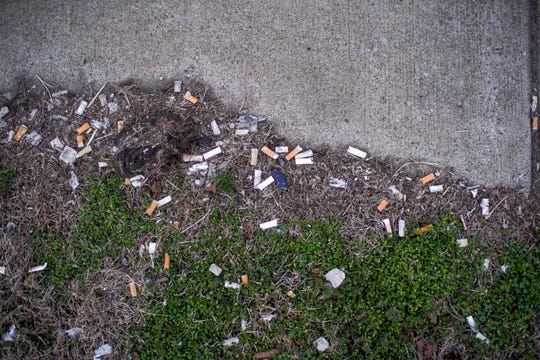 Tens of discarded cigarettes find a home squashes and pressed into the grass along a sidewalk on 2nd Street in Clarksville, Tenn., on Saturday, Feb. 15, 2020.