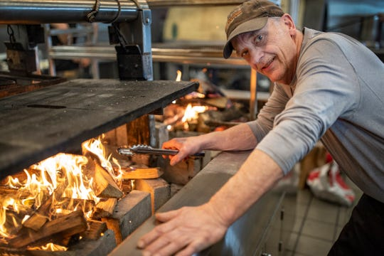 Tim Winterfield plans on riding his bicycle coast-to-coast to raise money for Gleaners Community Food Bank. He works at Magnet in Detroit stacking and preparing wood for their wood stove Monday, Feb. 17, 2020.