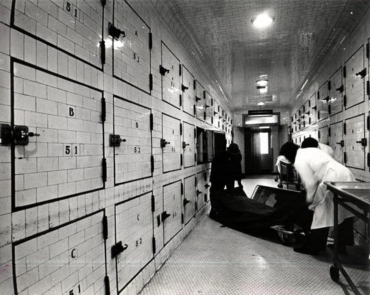 Wayne County Morgue Undertaker removing body from crypt section of Medical Examiners building in 1973.