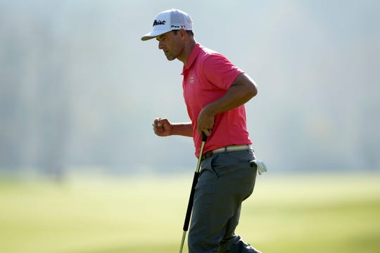 Adam Scott reacts after making a birdie putt on the 17th hole.
