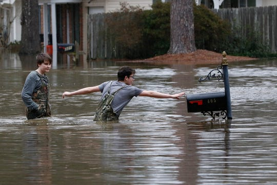 Blaine Henderson  reaches to tag a mailbox as Pearl River as he and his friend Jonah Valdez, both 12, play in the floodwaters of this northeast Jackson, Miss., neighborhood, Sunday, Feb. 16, 2020.