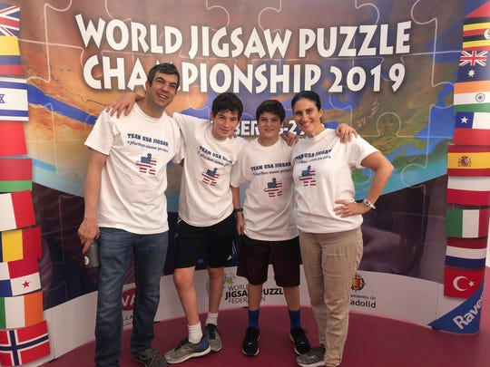 This photo taken on Sept. 28, 2019 and provided by A.J. Jacobs shows Jacobs, left, his sons Jasper, 15, Zane, 13, and his wife Julie Jacobs at the 2019 World Jigsaw Puzzle Championship in Spain. Jacobs, along with his wife and two sons, represented the U.S. in the jigsaw puzzle competition. Jacobs is currently at work on a book about puzzles that's expected to publish in 2021.