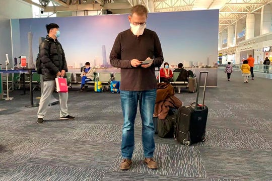 In this Feb. 1, 2020, photo provided by Ian Lipkin, Lipkin, director of the Center for Infection and Immunity at Columbia University, waits for his flight to Beijing at the Guangzhou airport in Guangzhou, China.