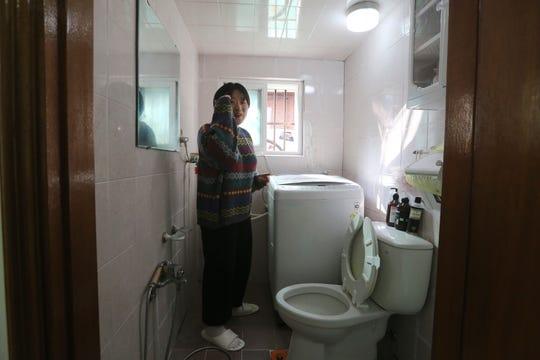 Kim Da-hye explains about the restroom, in her semi-basement apartment in Seoul.