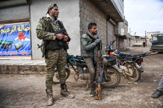 Syrian rebels sit outside Idlib, Syria, Saturday, Feb. 15, 2020. Syrian troops are waging an offensive in the last rebel stronghold.