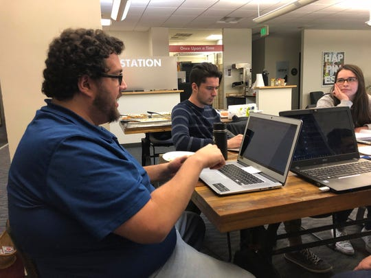 Ryan Mohrman, an energy industry software specialist, left, joins Ariel Lasry, an information system developer, center, and coder Kelsi Hoyle in working on a volunteer program project for a charity at a meeting of Code For Denver.