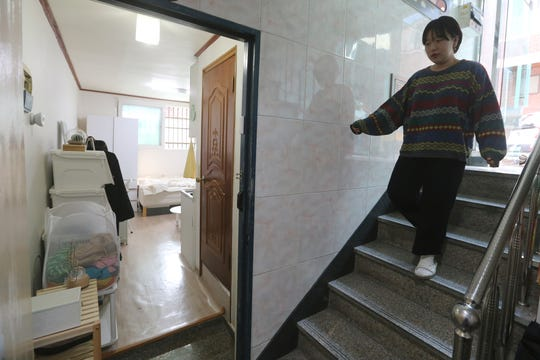 Kim Da-hye comes down the stairs to enter her semi-basement apartment in Seoul.