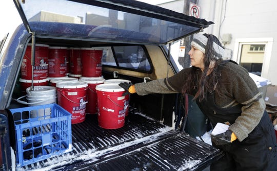 """Donna Yost, known as """"FarmHer Donna,"""" picks up buckets of food waste from Luna Cafe on Feb. 10, 2020 in De Pere, Wis."""