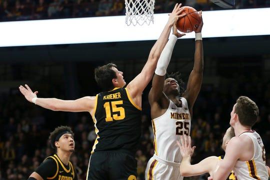 Iowa's Ryan Kriener (15) blocks the shot of Minnesota's Daniel Oturu on Sunday at Williams Arena, one of four blocks the Hawkeye senior made in a 58-55 win.