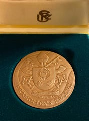 """Purdue Professor John Sheffield exchanged gifts with Pope Francis when they met on Feb. 7. Sheffield gave a copy of """"Ever True: 150 Years of Giant Leaps at Purdue University,"""" and the Pope gifted a medal commemorating his seventh year as pope."""
