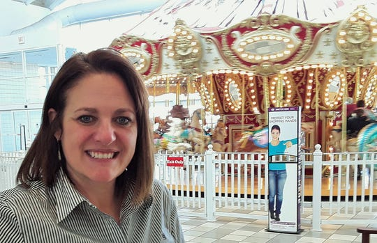 Monica Nadeau, senior general manager for Coral Ridge Mall, says entertainment features such as the carousel behind her are among several factors which have helped keep the mall a popular commercial center for 22 years.
