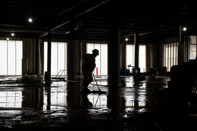 A man works on the floors inside the future home of Capital City Market on the 600 block of East Michigan Avenue in Lansing, Monday, Feb. 17, 2020. The Gillespie Group project includes plans for Meijer to operate one of its new urban grocery stores in the space.