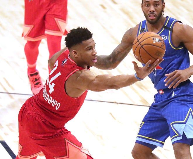 Giannis Antetokounmpo of the Milwaukee Bucks tries to save the ball as Kawhi Leonard looks on during the thuird quarter.