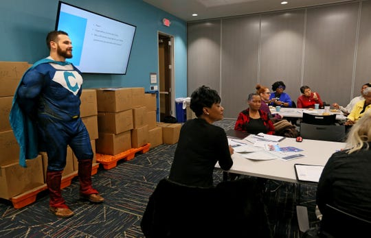 Donning a superhero costume, Matthew Dannenberg, left,  co-chair of the Greater Milwaukee Complete Count Committee and census director at Wisconsin Voices, listens as participants talk about why they are interested in having an active role in this year's census count during a training session in Milwaukee.