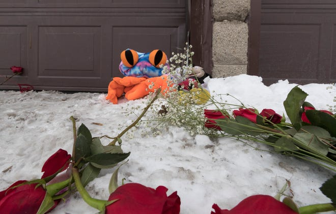 Flowers and stuffed animals lie outside a garage where the bodies of homicide victims Amarah J. Banks, 26, and her daughters, Zaniya R. Ivery, 5, and Camaria Banks, 4, were found on Feb. 16.