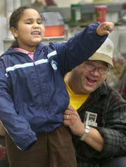 Joe Turecek greets 7-year-old Ashley Morris in 2002 on the corner of Fourth and State streets, where Morris was struck by a car about two months prior. Turecek, a hot dog vendor, rushed to her aid and helped lift the car off her leg.