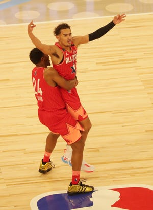 Team Giannis guard Trae Young of the Atlanta Hawks celebrates with Team Giannis guard Kyle Lowry of the Toronto Raptors after hitting a half-court shot at the halftime buzzer.