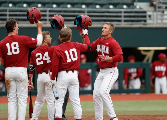 The Alabama baseball team celebrates at the plate during a 6-3 win over Northeastern on Sunday, Feb. 16, 2020 at Sewell-Thomas Stadium in Tuscaloosa.