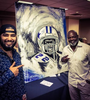 Artist Abel Garcia, left, poses with a portrait he created for Dallas Cowboys running back Emmitt Smith.