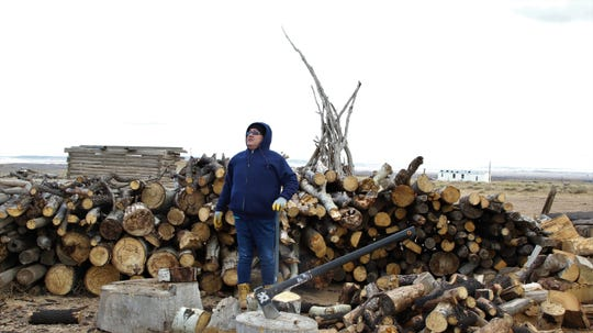 Faron Tsosie stands next to a pile of wood to be cut on Jan. 27, 2020, as a part of Naschitti Chapter's wood chopping program for the elderly, single parents and people with disabilities.