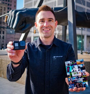 Canton resident Andy Gryczan holds the GoPro camera that helped him win a share of $1 million.