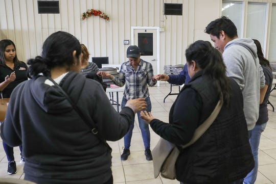 A small group of volunteers pray while organizing opposition to the creation of a new Immigration and Customs Enforcement Processing Center that could be opened in the agricultural community of McFarland, California, February 12, 2020.