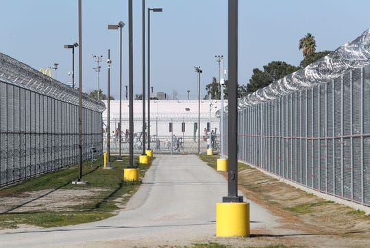Inmates can be seen from a public street outside the Golden State Modified Community Correctional Facility in McFarland, California, February 12, 2020.
