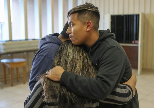 Maribel Ramirez hugs her two sons Jesus Gomez, left, and Eusebio Gomez, during a community meeting in protest of a possible new immigration detention facility coming to McFarland, Calif., February 12, 2020.
