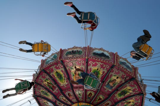 Children ride the swing at the 2020 Riverside County Fair and Date Festival Sunday, Feb. 16, 2020 in Indio, Calif. Riverside County sheriff's deputies arrested an 18-year-old suspect after a fight occurred at the fairgrounds on Feb. 21.