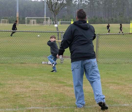 Sterling McCartney works on his batting skills with his father, Jason, at the Southwest Escambia Sports Complex on Bauer Road on Monday. Jason McCartney, a longtime resident of southwest Escambia County, welcomes the proposed changes to the area and sees the building of a new elementary school in the area as a positive sign of growth.