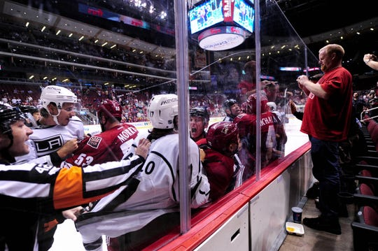 NHL referee Darcy Burchell grabs Los Angeles Kings left wing Daniel Carcillo (17), who grabs Phoenix Coyotes defenseman Paul Bissonnette (12) during a scuffle in the first period on Sept. 15, 2013.