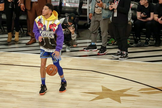 Devin Booker of the Phoenix Suns warms up before the NBA All-Star basketball game Sunday, Feb. 16, 2020, in Chicago. (AP Photo/David Banks)