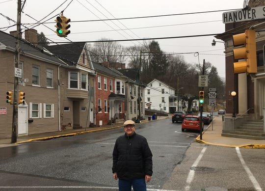 Jon Nicklow stands near the intersection with the suspended signal light in Glen Rock. The signal is believed to be the last of its kind in York County.