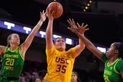Southern California forward Alissa Pili, center, shoots as Oregon guard Sabrina Ionescu, left, and forward Ruthy Hebard defend during the first half of an NCAA women's college basketball game Feb. 16, 2020, in Los Angeles.