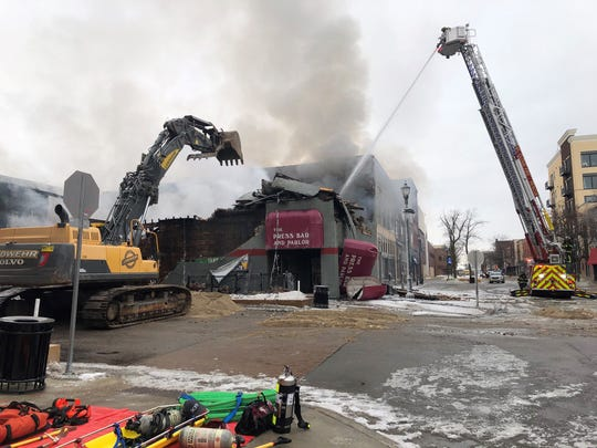 Crews knocked down walls at the Press Bar in downtown St. Cloud Monday following the early morning fire.