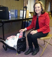 Mina Gruccio, chairwoman for domestic violence donations for the Woman's Club of Vineland, fills a bag with donations collected by club members during February.