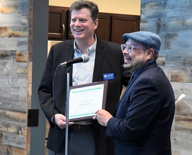 """Self-Help Enterprises CEO Tom Collishaw accepts a certificate recognizing Self-Help's """"vital role in providing housing to the Goshen community"""" from Tulare County Supervisor Eddie Valero. Sequoia Commons, an affordable housing complex in Goshen, had its grand opening Friday, Feb. 14, 2020."""