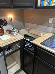 A photo of partial work done on a kitchen remodel at the Roberts home. They were left with no counter tops, cabinet drawers or doors, unfinished electrical work and unfinished plumbing.