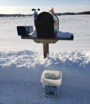 An old detergent bucket sits next to the mailbox with the day's mail inside ready to take inside and peruse.