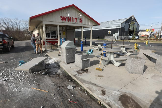 Terry Wells, owner of Whit's Frozen Custard, left, and Bryan Lewis clean up the store's outdoor seating area after a vehicle crashed into it. The pickup, driven by Cody A. Basehart of Nashport, struck and killed a woman walking down Maple Avenue after hitting a power pole.