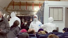 In this image from a video taken on Monday, Feb. 17, 2020, U.S. passengers who evacuated off the quarantined cruise ship the Diamond Princess and officials wait for the takeoff of a Kalitta Air airplane bound for the U.S.