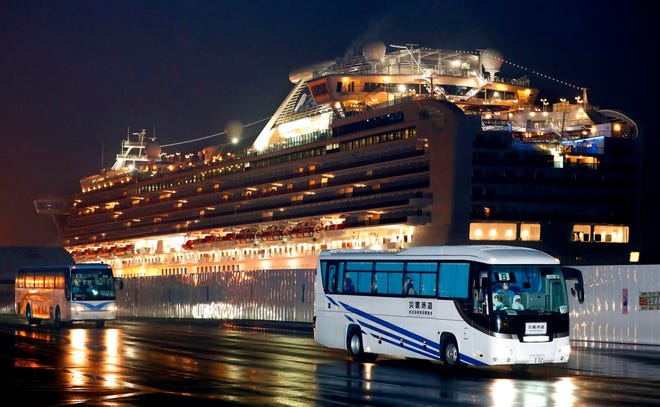 Buses carrying U.S. passengers who were aboard the quarantined cruise ship the Diamond Princess, seen in background, leaves Yokohama port, near Tokyo, early Feb. 17, 2020. The cruise ship was carrying nearly 3,500 passengers and crew members under quarantine.