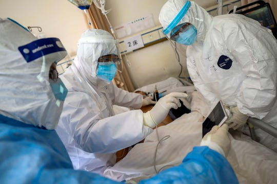 Medical personnel scan a new coronavirus patient at a hospital in Wuhan, China, on Feb. 16, 2020.