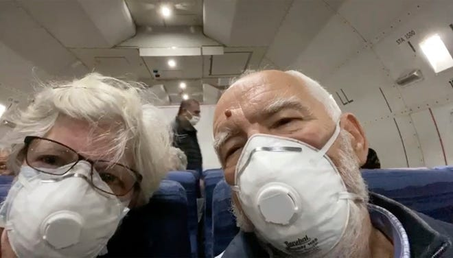 In this image from a video taken on Monday, Feb. 17, 2020, Cheryl Molesky, left, and Paul Molesky, who evacuated off the quarantined cruise ship the Diamond Princess, film selfie video aboard a Kalitta Air plane bound for the U.S., at Haneda airport in Tokyo.