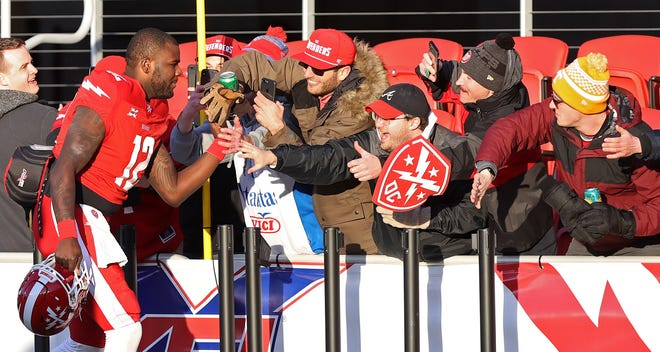DC Defenders quarterback Cardale Jones shakes hands with fans while leaving the field after a game against the New York Guardians.